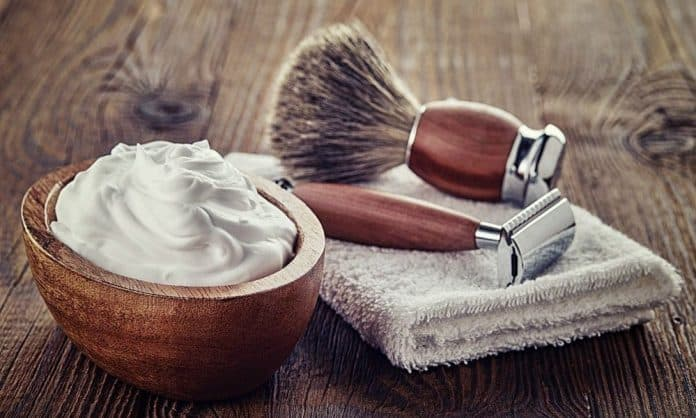 shaving cream and shaving items on a table with a towel