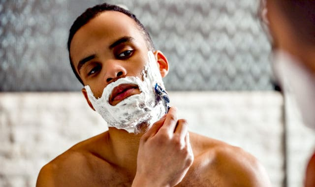 man shaving his facial hair