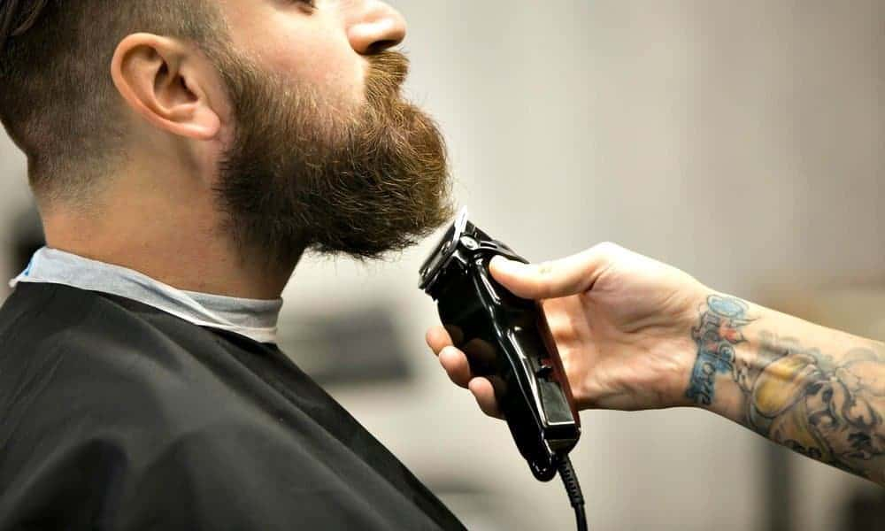 barber using beard trimmer on mans facial hair