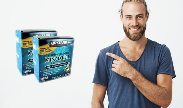 man with beard points at two packs of kirkland minoxidil