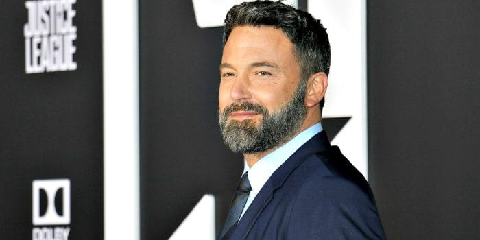 Ben Affleck smiling in a blue suit with well-kept beard