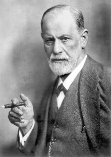 Sigmund Freud looking intensely into the camera with a cigar on his hand.