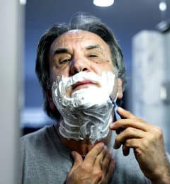 old man shaving by the mirror