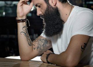 man with bushy beard looking down