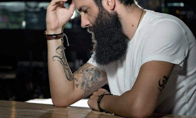 man with bushy beard looking down