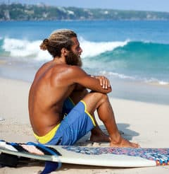 man with a beard on a beach with a surfboard