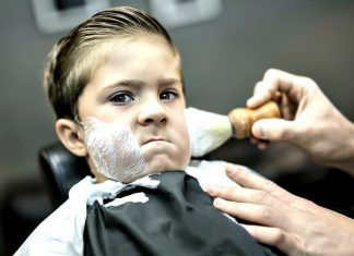 little kid getting a shave at a barber shop