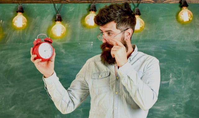 man with facial hair looking at a clock
