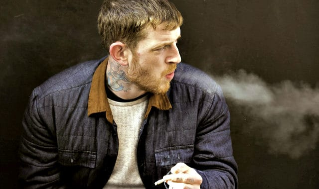 short bearded man smoking a cigarette