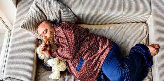 fat man with a soft looking beard sleeping in silky pyjamas