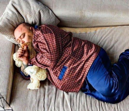 fat man with a soft looking beard sleeping in silky pyjamas