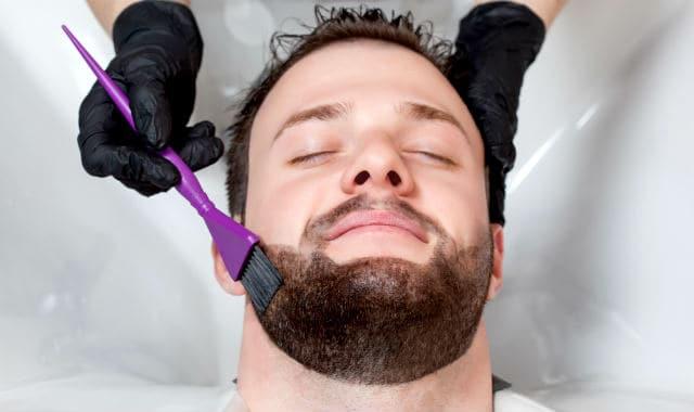 man getting his short beard dyed at salon