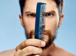 man seeing fallen beard hair on a comb