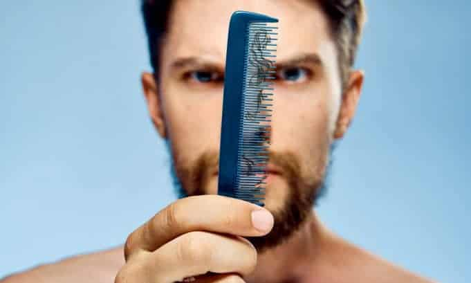 man seeing fallen beard hair on a comb