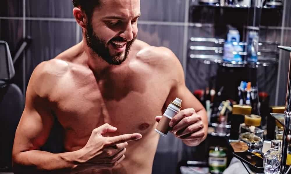 man showing a bottle of beard growth serum