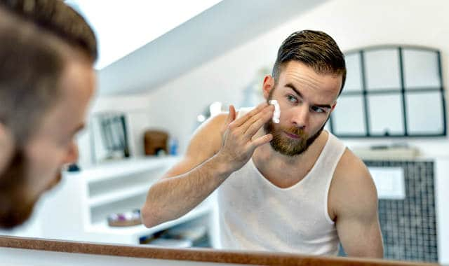man using a beard moisturizer on his face