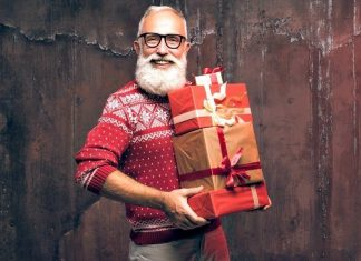 man with a beard in christmas spirits holding a stack of gifts