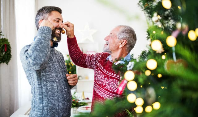 old man fixing up a christmas bauble to sons facial hair