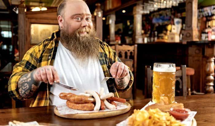 fat bearded man enjoying food