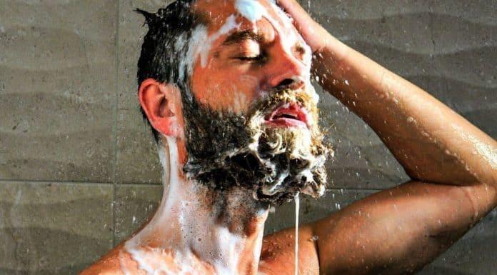 man washing his facial hair with shampoo