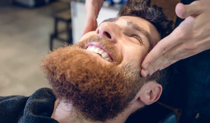 man getting his beard exfoliated at barbershop