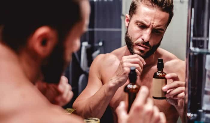 man staring at a bottle of beard growth spray