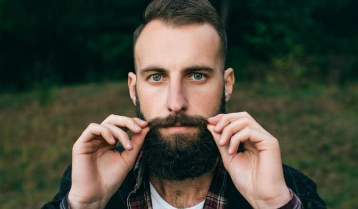 bearded man applying beard balm