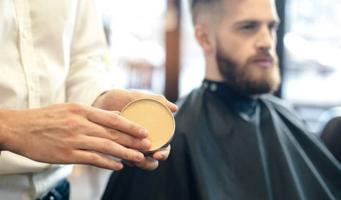 barber using beard wax on client