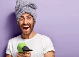 bearded man pointing a blow dryer