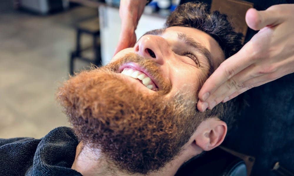 man getting his beard exfoliated