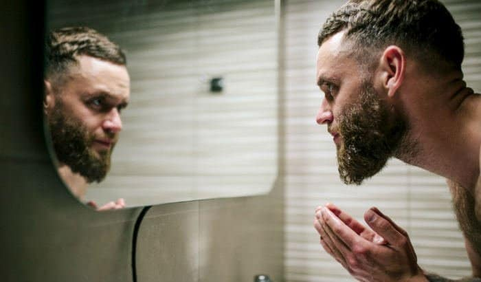 man scrubbing his beard