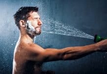 man washing his beard with a garden hose
